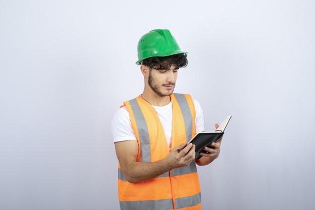 jeune-homme-ingenieur-casque-vert-lire-notes-fond-blanc-photo-haute-qualite_114579-41603.jpg