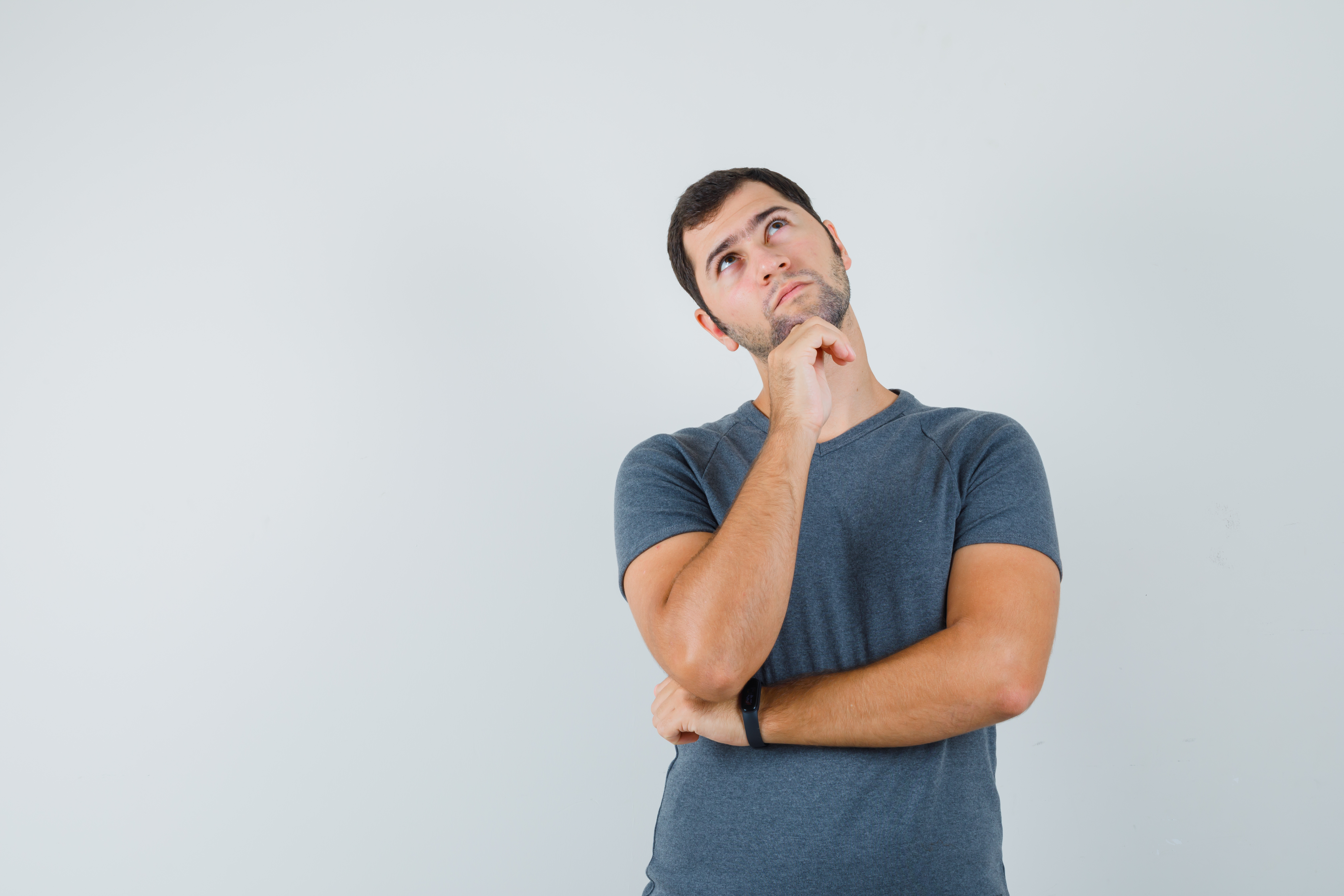 young-male-in-grey-t-shirt-propping-chin-on-hand-and-looking-pensive.jpg